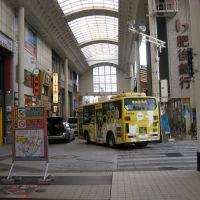 アーケード付き商店街に路線バスが乗り入れる風景, Кумамото