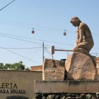 Two cablecars are crossing behind a statue of a worker with a hammer, Закатекас