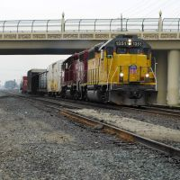 A couple of locomotives haul a short line of freight down the Union Pacific Railroad tracks underneath the P St overpass, 12/2012, Модесто