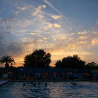 Sunset over synchronized swimmers, and photographer balanced on diving board, Гайнесвилл